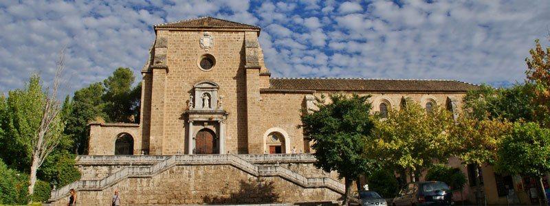 Fachada de un monasterio en piedra, con escalinata empinada que conduce a la portada principal, escalinata simétrica a derecha e izquierda, en la portada hay arco de medio punto con puerta cerrada y encima una hornacina con la escultura de un santo. A la izquierda se ve el edificio que guarda el claustro interior
