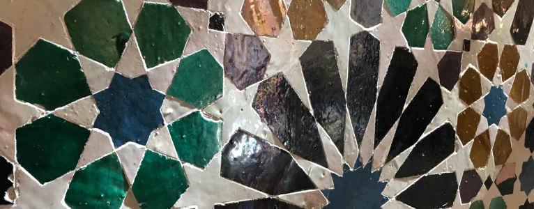 Detalle de azulejos en forma de estrella de ocho puntas de muchos colores: verde, negro, marrón, blanco