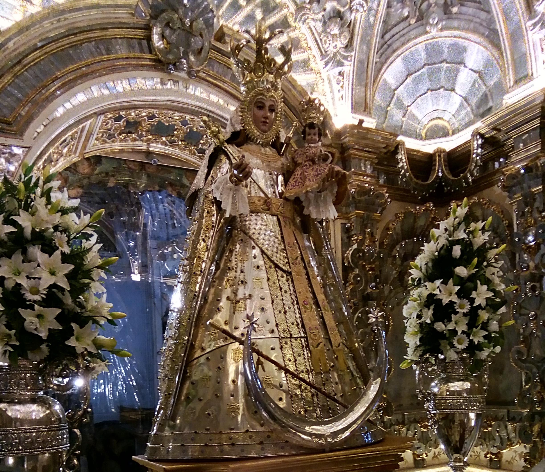 Escultura de la Virgen del Rosario, vestida con un vestido metálico dorado y con incrustaciones de piedras preciosas y decorado alrededor de flores blancas y techo de mercurio, cristal con reflejos