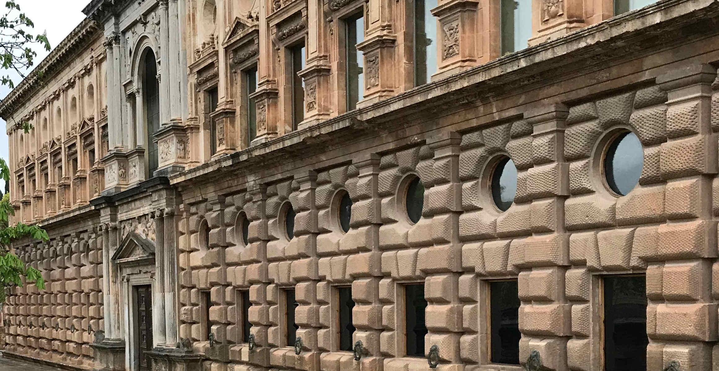 Fachas principal de un palacio estilo italiano, de dos plantas, zona baja almohadillada con ventanas y óculos, zona alta con ventanas y entrada principal hecha en piedra gris con bonitas columnas y relieves en piedra