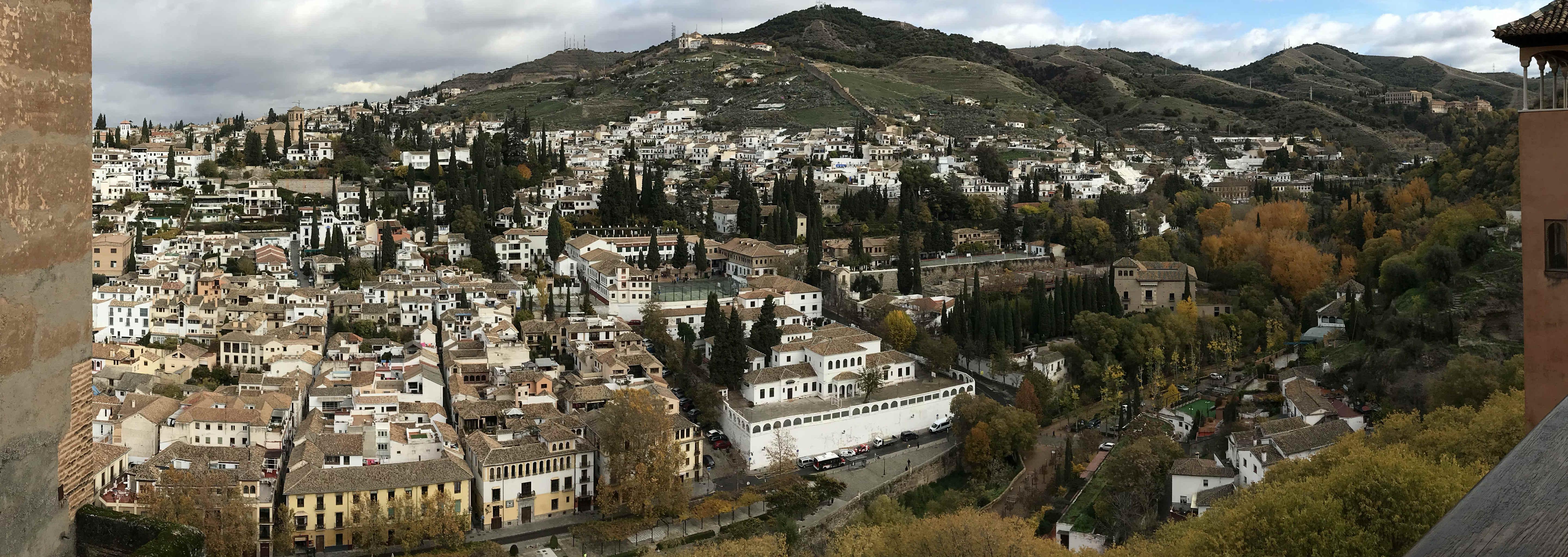 Visita panorámica de una montaña llena de casas apiñadas de color blanco y muchos jardines con cipreses