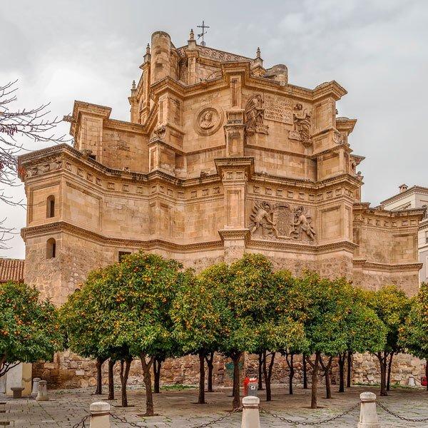 Ábside de un monasterio visto desde fuera, con decoración de escudos de armas, y 4 cuerpos en altura donde sobresale en el último el tejado de la iglesia con cruz en la parte alta