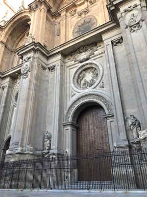 Fachada de una catedral con portada de piedra, arco de medio punto y decoración de relieves hechos en piedra con un medallón de la Virgen encima de la puerta