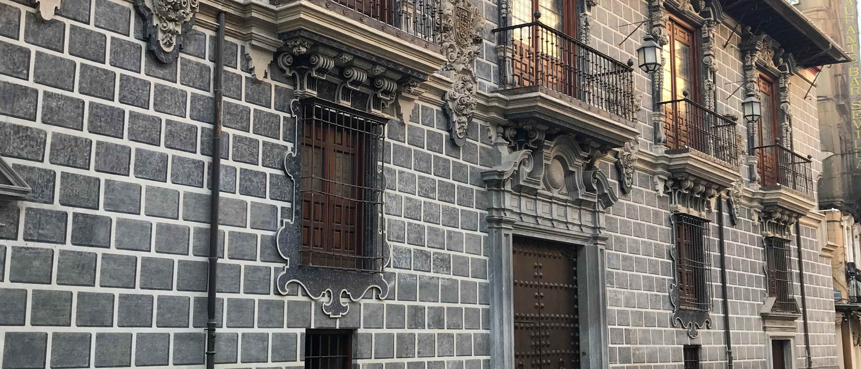 Foto fecha de un edificio lateral, se ve a la izquierda un muro de grandes bloques de piedra pintados en negro y blando, con balcones en la planta alta y ventanas en la parte baja, se ve la puerta en el centro cerrada