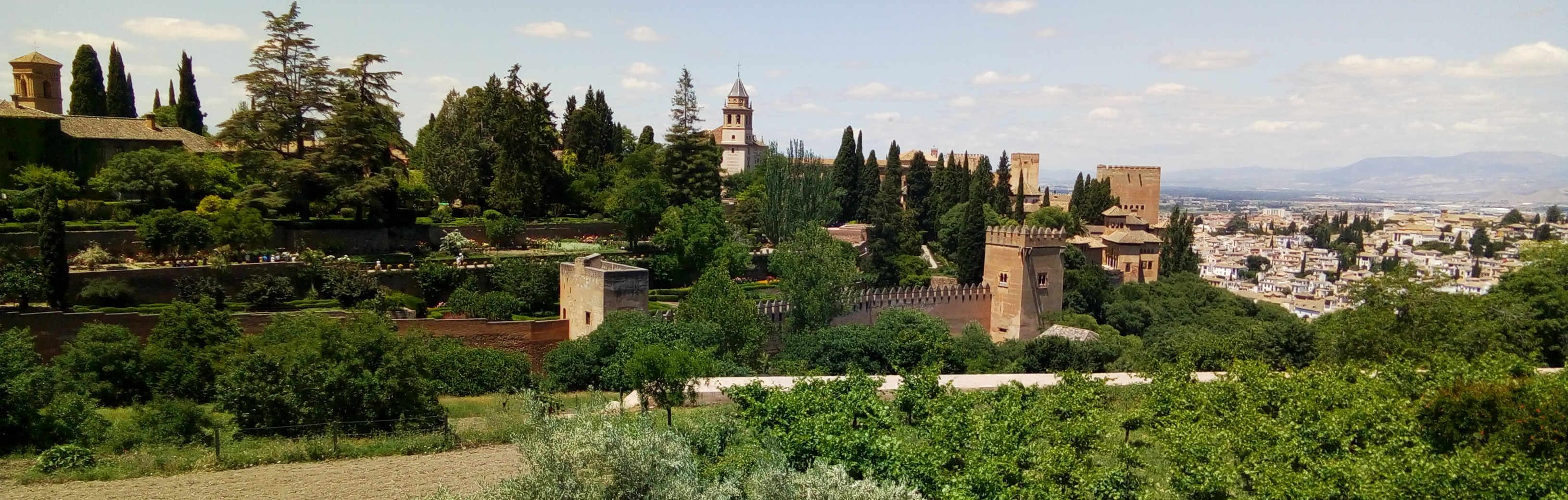 Foto de huertas y jardines, en el fondo murallas, torres, el campanario de una iglesia y el tejado de un edificio al izquierda, mientras que a la derecha al fondo se ven casas blancas apiñadas en la lejanía