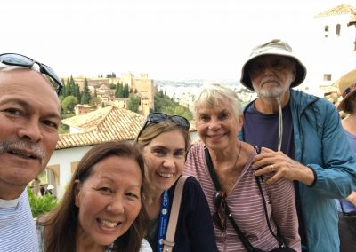 Picture of five people smiling, with the towers of the Alhambra in the background