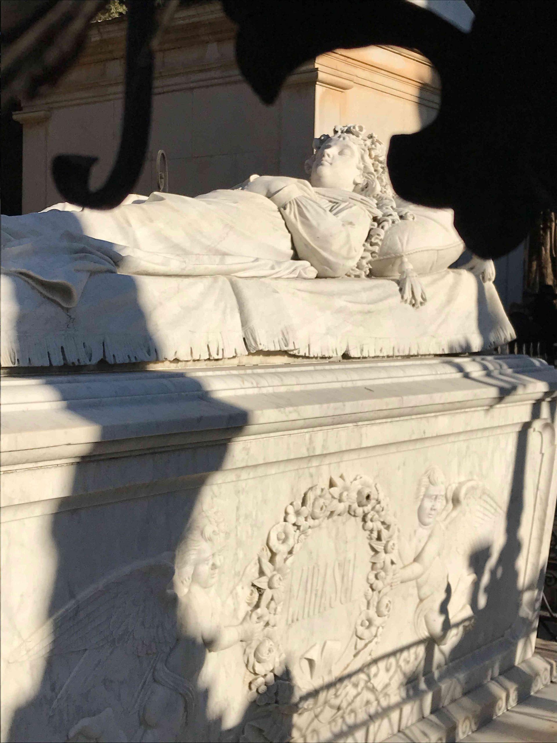 Sepulcro de mármol con una mujer espulpida arriba y pelo largo, brazos cruzados en el pecho