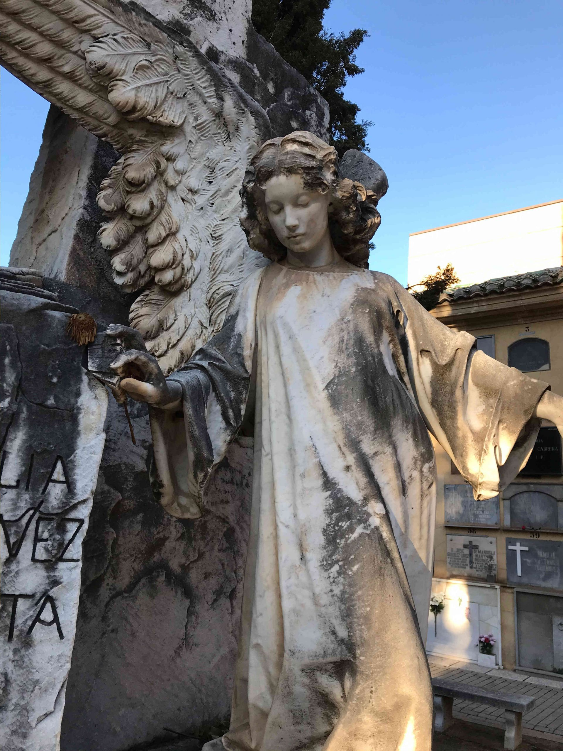 Escultura de mármol blanco de un niño convertido en ángel con algas, arrastrando una cruz de mármol en su hombro izquierdo